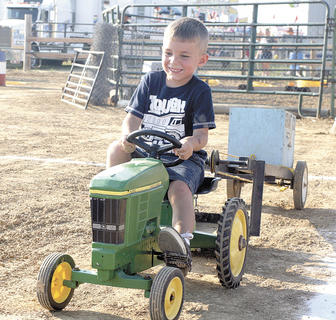 Coleman Caldwell tries his best in the pedal tractor pull at the Grant County Fair.