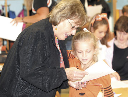 Brenda Stanley talks with her granddaughter, second grader Grace Stanley, about her class work.