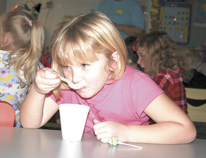 "Williamstown Elementary first grader Tammy Ashcraft enjoys hot chocolate during Mrs. Barker's ""Polar Express"" pajama party."