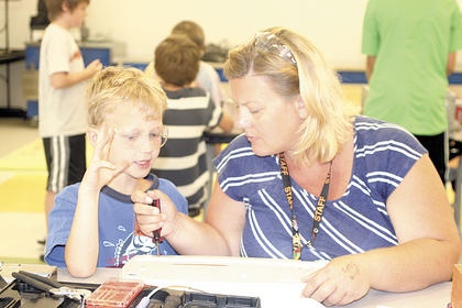 WES teacher LeAnn Fields helps her son, Walker, take apart an electronic device during Camp Invention.