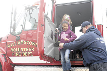 Williamstown Elementary student Cariel Smith gets a helping hand out of a fire truck after taking a tour.