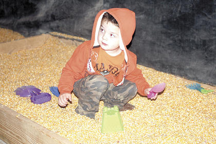 DRE preschooler Trent Blake likes playing in the corn box with a shovel and a bucket.