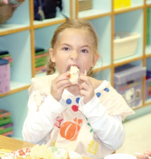 Second grader Avery Hornbeck takes a big bite of a piece of cake. 