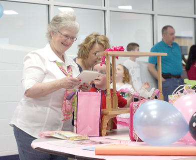 CMZ Family Resource Center director Kay Hughett, left,  opens a card during her Rock Around the Clock retirement party. The themed party featured cake, punch, a DJ playing oldies music and several poodle skirts.