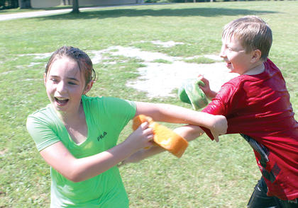 Chelsey Drysdale and Jase Crouch use sponges to drench each other during a water fight at Summer Splash camp at Grant County Park in Crittenden. Photo by Bryan Marshall
