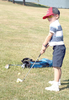 Joshua Forman looks at his target before teeing off at the junior golf class at Eagle Creek Country Club, organized by Grant County Parks and Recreation.