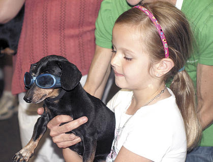 Delaney Newcomb holds Woody as he looks on to the crowd in his goggles.