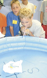Tyler Osborne uses a straw to try to move his paper ship in the inflatable pool as Brock Houchens and other fellow campers watch.