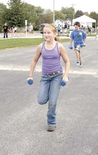 Sarah Mullins of Grant County Middle School holds weights while running a relay race.