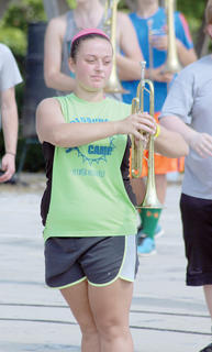 Brooklynn Henson braves the heat while holding her trumpet during WHS Band of Spirit summer camp.