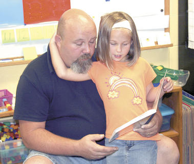 Abigail McKenney reads a book with her dad, Keith McKenney.