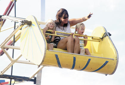 Barb Goetz of Williamstown waves from the top of the ferris wheel with 3-year-old daughter Mia and her friend, 5-year-old Emily Mann. Photo by Camille McClanahan