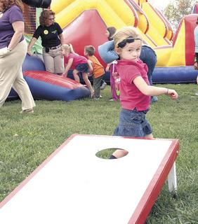 Emily Mann of Williamstown concentrates on her throw while playing cornhole.