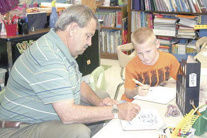 First grader Adam Beck watches as his grandpa, Gary Theurer, draws a picture.