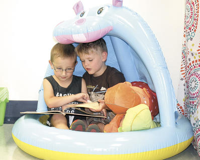 Keaton Connelly and Benjamin Carr read a book together underneath an inflatable hippo pool at CMZ Kinder Camp.