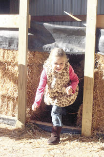 CMZ student Makenna Simpson plays in the hay bale maze. 