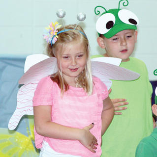 "Joie Ginder dresses as a butterfly while Rylie Biddle is a caterpillar in the CMZ kindergarten play ""Bugs"" during the promotion ceremony."