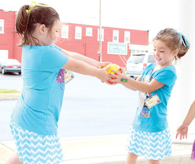 Twin sisters Maci and Madison Spivey hurry to pass the ball like a hot potato before the water balloon inside bursts