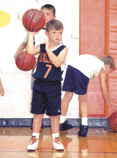 Caden Smithers holds the ball high as he listens for instructions for the next drill.