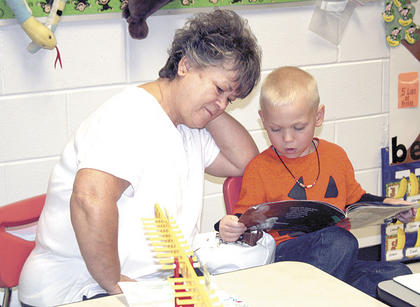  Debbie Wolfe listens intently as her grandson, first grader Isaiah Spencer, reads a book to her.