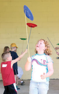 Madison Beatson concentrates on spinning a plate on a stick during a Circus Mojo station at Summer Splash.