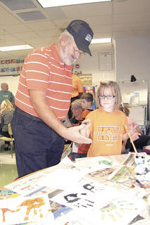 First grader Phoenix Button paints the hand of her grandfather, Robert Adams.