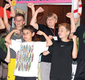 Adam March, Dylan Cripe, Bryson Stanley and Kyron Held show off their muscles while singing and dancing to a song at Williamstown Baptist's Vacation Bible School.