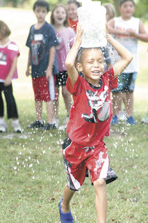  Isaiah Gillium gets wet running in a relay while holding a hole-filled bucket of water on his head. 
