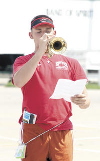 Alec Dalton checks his music sheet to make sure he is hitting the right notes while practicing at band camp.