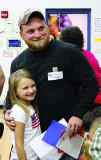 MCE's Isabella Kelly gives a card and hug to her father, a veteran, Jon Kelly, as the other students shake other veterans' hands at the end of the celebration.