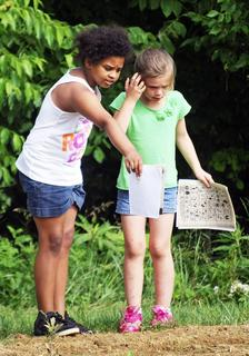 Makayla White and Ashlyn White debate over what animal tracks they see in the dirt.