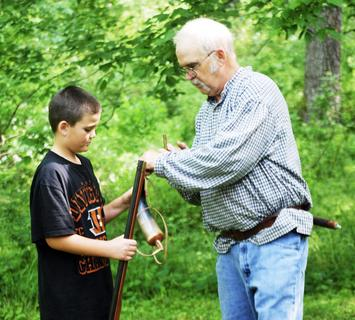 Lamar Fowler, Grant County Extension Agent for 4-H and youth development, explains to Matthew Jones how to shoot a muzzle loader.