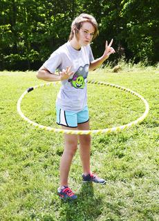Janna Saylor hula-hoops as she flashes the peace sign.