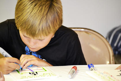 Jaxon Kinman concentrates on his art project.