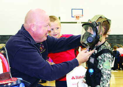 Coy Lunsford of the Dry Ridge Fire Department helps Andrew Trammell try on a air breathing mask.