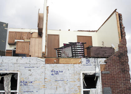 A baby's crib dangles  from the rubble left after an F3 tornado, with estimated wind speeds of 123 miles per hour, ripped the front off this apartment building on Barley Circle in Crittenden.