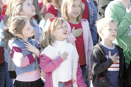 WES kindergartners Gracie Shepherd, Bradie Rogers and Aiden Ousley participate in the Pledge of Allegiance during a Veterans Day ceremony.