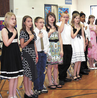 Kylie Wood, Kinley Wilson, Christian Wilson, Bailey Wainscott, Daniel Vincent and Samantha Schawe say the Pledge of Allegiance during DRE's fifth grade graduation.