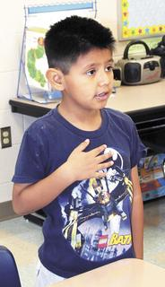 Sherman Elementary first grader Eric Morales stands for the pledge