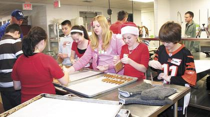 Tanner Dalton, Morgan Thompson, Brandi Anglin, Katelynn Kidwell and Braydon Dungan, all sixth grade students at Williamstown Middle School, help the Kiwanis prepare sausage for Breakfast with Santa on Dec. 3.