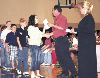 Megan Robinson accepts her diploma from David Fordyce, principal at Sherman Elementary, during the fifth grade graduation ceremony.