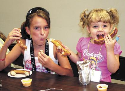 Tyanna Honeycutt and Alayna Duggins enjoy pretzels with cheese during snack time.