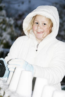 Emily Wallace, 10, makes a snow wall using a styrofoam cup while she waits for Santa&#039;s arrival.