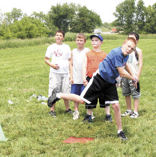 Shane Bently whips a ball as classmates Fred Harris, Ben Scharf and Lucas Allnutt watch.