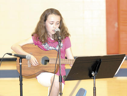 Brooke Surrett sings and displays her skills as she plays guitar at the talent show.