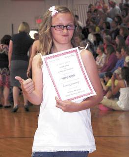 Summer Dearing gives her parents a thumbs up after receiving her diploma.