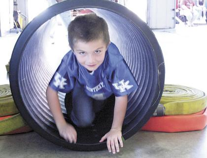 Brayden Taylor crawls through a tunnel.