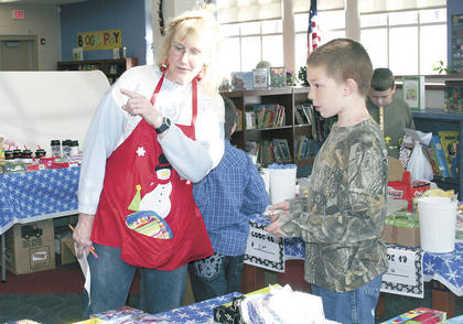 Parent volunteer Pam Mendey helps student Shane Bentley pick out a gift during the Sherman Elementary Santa Shop.