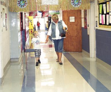 Jordan McKinney and his grandmother walk hand-in-hand down the hallway.