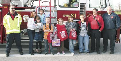 Members of the Dry Ridge and Williamstown Fire Departments brought students at Sherman Elementary to school in fire trucks for reading the most books during a reading promotion by SES Media Specialist Cheryl Million. Pictured are Lee Burton, DRFD, Million, Isabella Iles, Layton Wallace, Nicholas Parrott, Bethany Thomas, McKenzie Mocahbee, Daniel Meredith, Calvin Crupper of the DRFD and Williamstown Fire Chief Les Whalen.